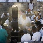 Haitians gather at a tombstone on All Saints Day